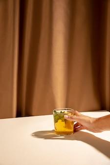 La mano della persona che prende il vetro di cocktail sullo scrittorio bianco