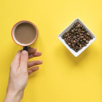 La mano della persona che prende la tazza di caffè con i chicchi di caffè arrostiti su fondo giallo