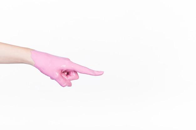 La mano della persona con la pittura rosa che indica il dito su fondo bianco