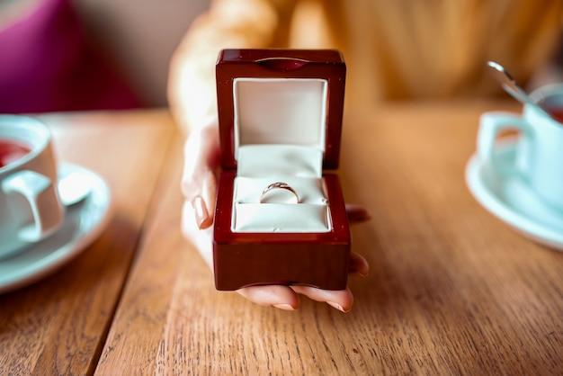 La mano della persona femminile tiene la scatola con la vista del primo piano dell'anello nuziale dorato