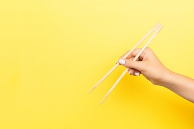 La mano della ragazza che mostra le bacchette su giallo. cucina asiatica con vuoto