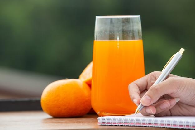 La mano della ragazza che scrive un libro con succo d'arancia e arance