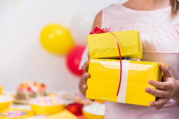 La mano della ragazza che tiene i contenitori di regalo gialli con il nastro rosso