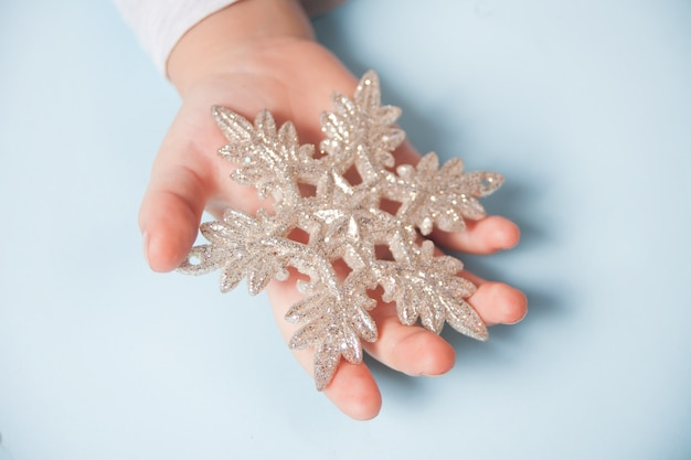 La mano della ragazza che tiene un grande fiocco di neve della decorazione di natale in mani sull'azzurro