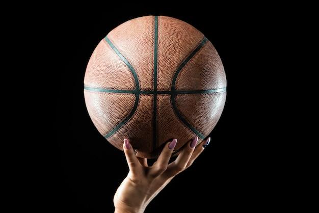 La mano della ragazza che tiene una palla da basket.