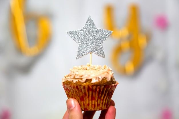 La mano della ragazza tiene cupcake ai mirtilli con topper stella glitter argento