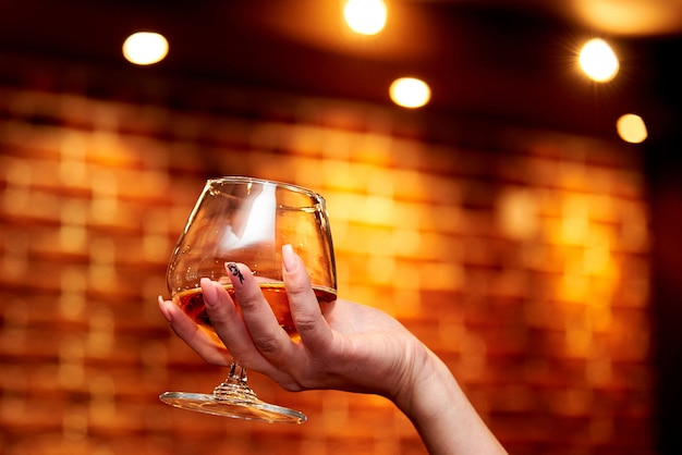 La mano della ragazza tiene un bicchiere di cognac su uno sfondo sfocato.