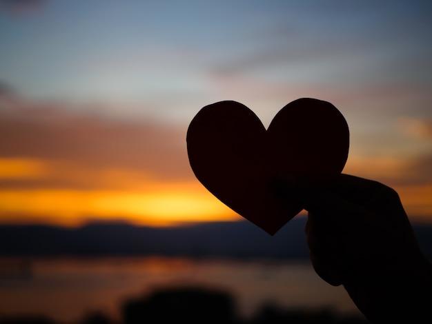 La mano della siluetta sta alzando il cuore di carta rosso durante il tramonto