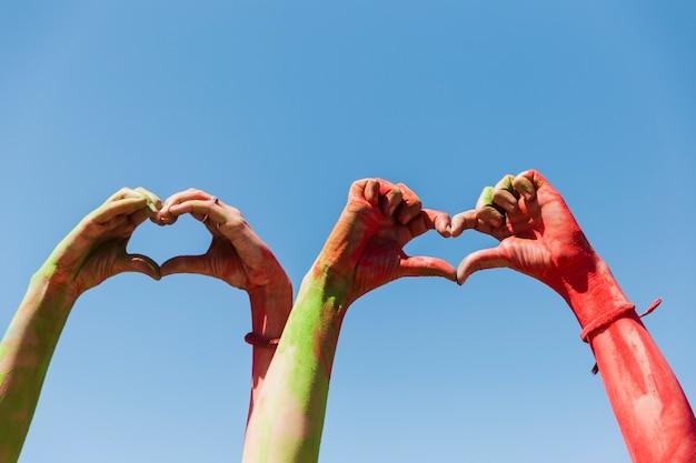 La mano delle donne che mostra la forma del cuore contro il cielo blu