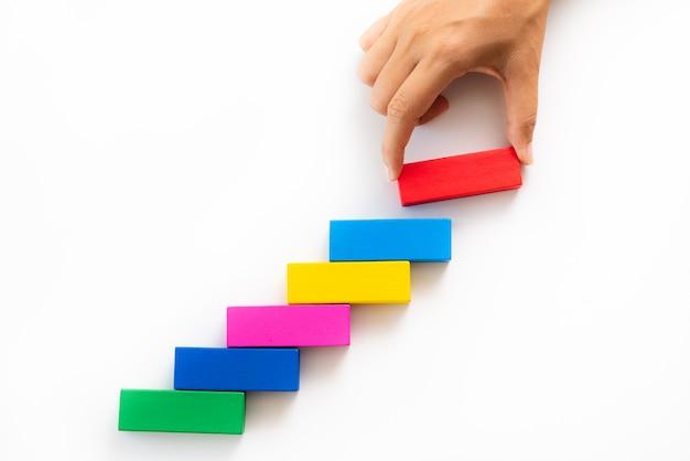 La mano delle donne ha messo il blocco di legno rosso sotto forma di una scala