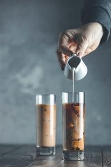 La mano delle donne sta versando la panna acida fatta in casa dal barattolo al bicchiere con caffè freddo freddo e ghiaccio. bevanda fredda di estate su una tavola di legno scura e su un fondo grigio con lo spazio della copia