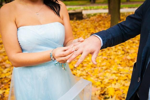 La mano dello sposo che mette una fede nuziale sul dito della sposa