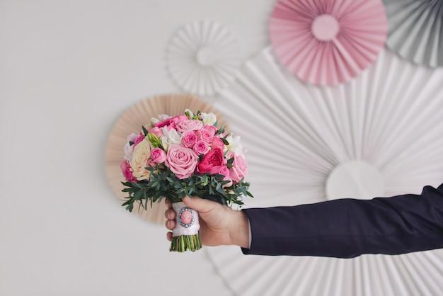 La mano dello sposo tiene il bouquet da sposa di rose con una spilla sullo sfondo