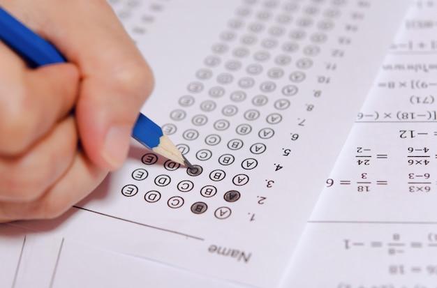La mano dello studente che tiene la matita che scrive la scelta selezionata sui fogli di risposta e sui fogli di domande di matematica.