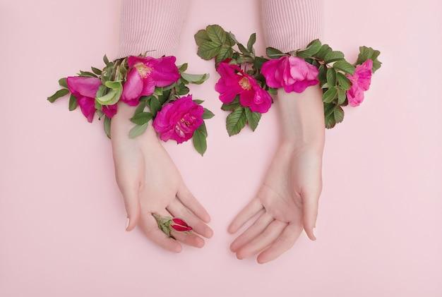 La mano di bellezza di una donna con i fiori rossi si trova sulla tavola, fondo di carta rosa. prodotto cosmetico naturale e cura delle mani, idratazione e riduzione delle rughe, cura della pelle