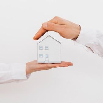 La mano di due persone di affari che protegge la casa di modello miniatura isolata su fondo bianco