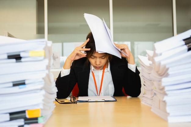 La mano di riposo della donna di affari sugli occhi capi si chiude con il mucchio di lavoro di ufficio.