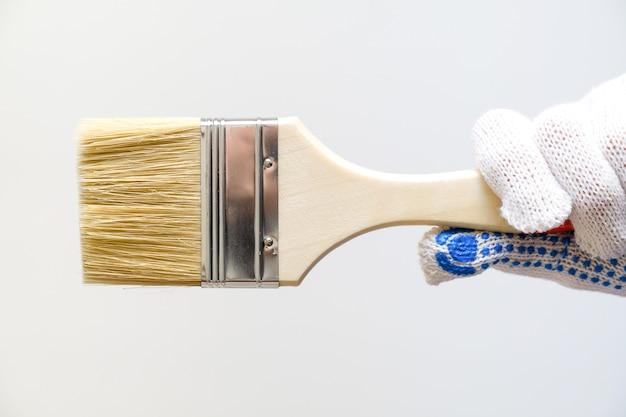 La mano di un tecnico tiene un pennello. il concetto di riparazione, costruzione e miglioramento domestico e professionale.