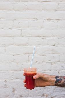 La mano di un uomo che tiene il frullato in tazza di plastica monouso con paglia contro il muro