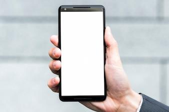 La mano di un uomo d'affari che mostra lo schermo di visualizzazione bianco di uno smartphone contro il contesto vago