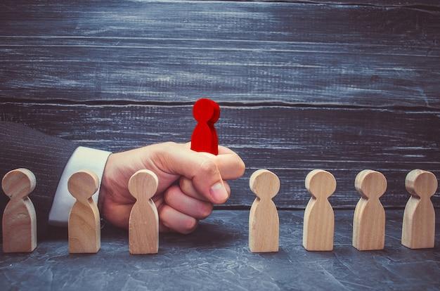 La mano di un uomo d'affari prende una figura di legno rossa di un uomo. il concetto di ricerca