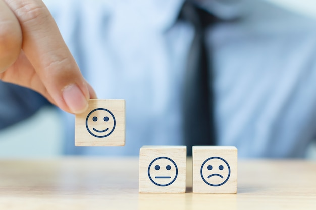 La mano di un uomo d'affari sceglie una faccina sorridente sul cubo di blocco di legno, i migliori servizi aziendali eccellenti valutazione esperienza cliente, concetto di sondaggio di soddisfazione