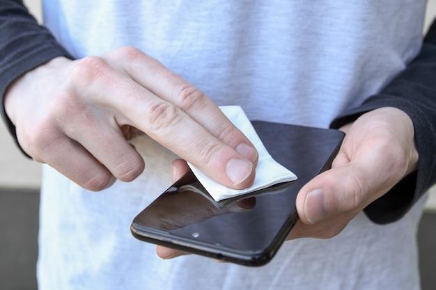 La mano di un uomo tiene e scatta uno spray disinfettante e disinfetta il telefono per disinfettare varie superfici che le persone toccano. gel antibatterico antisettico per le mani