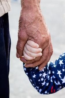 La mano di un vecchio e la mano di una bambina. nonno e sua nipote