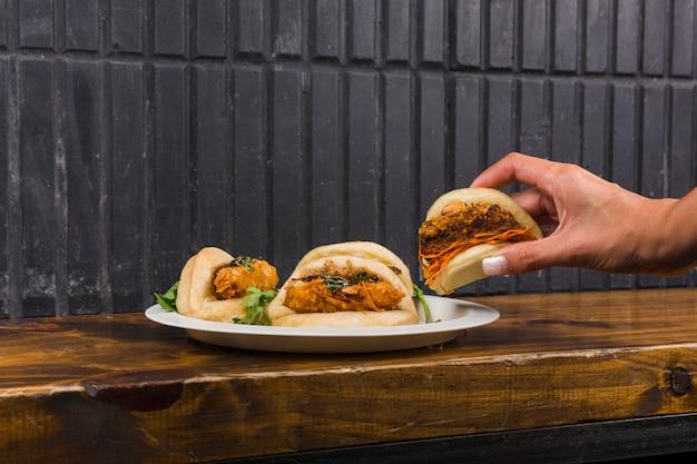 La mano di una donna che tiene il gua bao inforna il pane sul piatto bianco sopra lo scrittorio di legno