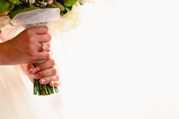 La mano di una donna con la fede nuziale mentre si tiene il suo bouquet, abbondanza di spazio bianco copia.