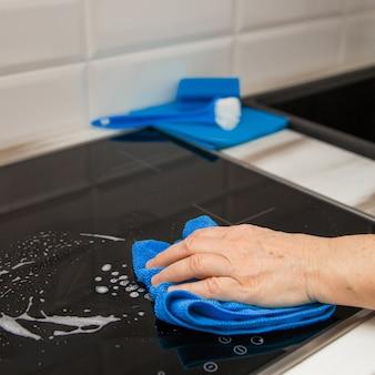 La mano di una donna con un panno blu in microfibra sfrega un piatto di vetro ceramico in cucina