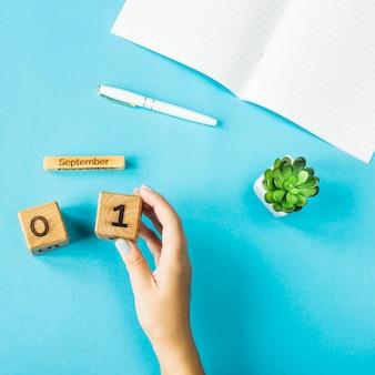La mano di una donna tiene un calendario di legno con la data del 1 ° settembre