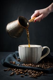 La mano di una donna versa il caffè turco dai turchi in una tazza.