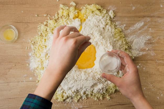 La mano di una persona aggiungendo il pizzico di sale nella farina e formaggio grattugiato per la preparazione di gnocchi italiani sulla scrivania in legno