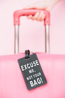 La mano di una persona che maneggia la valigia di viaggio con non il tag della tua borsa su sfondo rosa