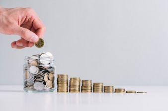 La mano di una persona che mette i soldi in barattolo di vetro vicino a monete impilate diminuendo