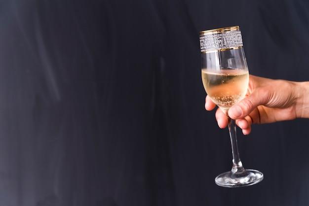 La mano di una persona che tiene il vetro elegante del champagne con la bolla contro il fondo nero