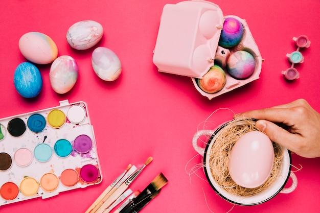 La mano di una persona che tiene l'uovo di pasqua rosa nella pentola con la scatola dell'acquerello; pennello e scatola di uova su sfondo rosa