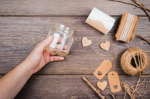 La mano di una persona in possesso di una bottiglia di vetro vuota con nastro di pizzo; forma a cuore in legno; tag e spool thread sul tavolo