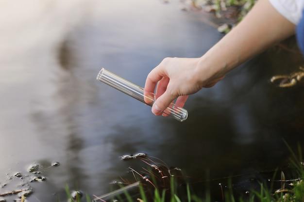 La mano di uno specialista attinge acqua in un pallone da un fiume per ulteriori ricerche in laboratorio. controlla il livello di inquinamento dell'acqua. messa a fuoco selettiva