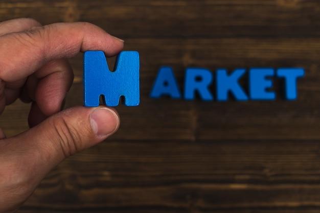La mano e il dito sistemano le lettere del testo della parola del mercato su legno