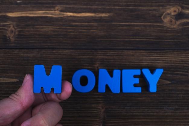 La mano e il dito sistemano le lettere di testo della parola soldi