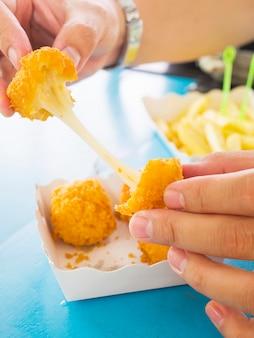 La mano è in possesso di una palla di formaggio stretch pronta per essere mangiata