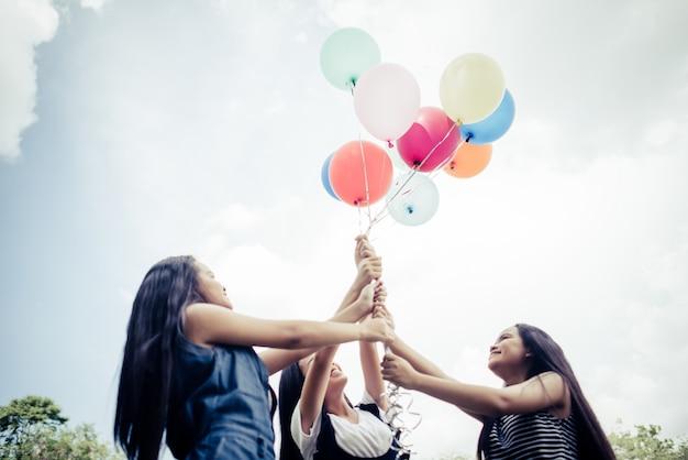 La mano felice delle ragazze di gruppo che tiene i palloni multicolori