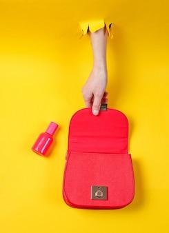 La mano femminile apre la borsa in pelle rossa con bottiglie di profumo attraverso il foro di carta gialla strappata. concetto di moda minimalista