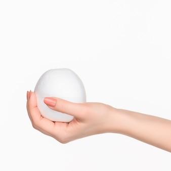 La mano femminile che tiene ovale in polistirolo bianco vuoto