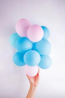 La mano femminile che tiene un piccolo insieme rosa e blu ballaons lika una nuvola su fondo bianco
