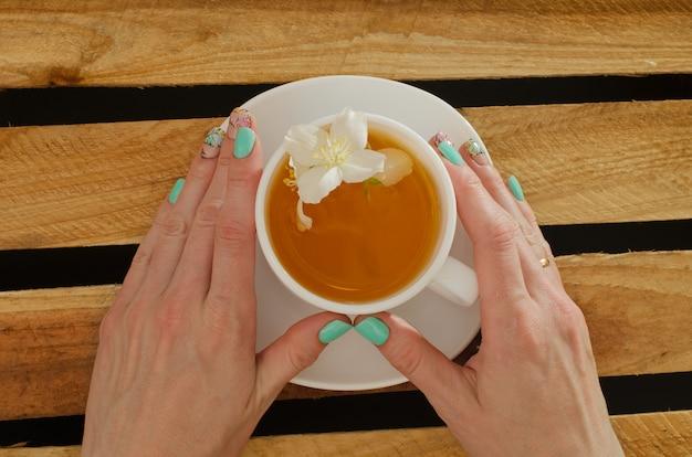 La mano femminile che tiene una tazza di tè e il gelsomino fiorisce, vista superiore sulla a delle plance di legno