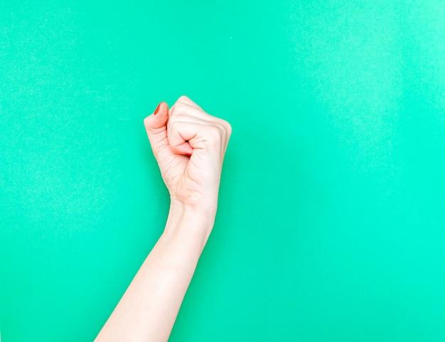 La mano femminile con ha serrato un pugno sul fondo isolato di colore verde del turchese.