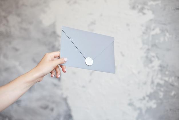 La mano femminile dà alla busta d'argento una cartolina d'auguri dell'invito di nozze su un fondo grigio.